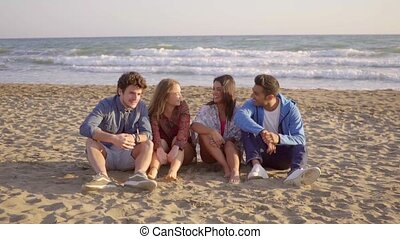 Meet With Friends. - Four young people sitting on the sandy...