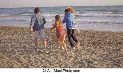 Young People Running On The Beach - Three girls and two boys...