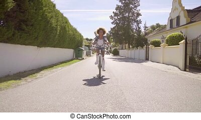 Girl Riding With Feet Out On A Bicycle - Young mixed-race...