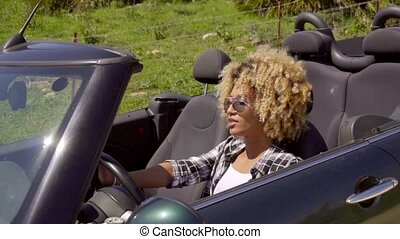 Trendy young woman driving her cabriolet with the top down...