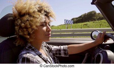 Attractive young African American woman driving