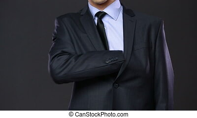 Firearms and security topic: a man in a black suit holding a...