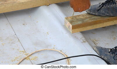 Screwing a screw into a wood board, close up - Putting some...
