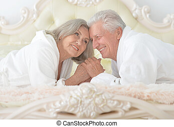Senior couple in bed - happy Senior couple reading in a bed