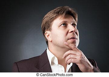 Pensive man looking up - Headshot pf adult businessman...