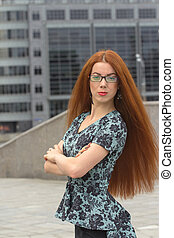 Red-haired woman on the background of office building -...