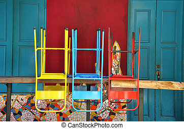 Colorful chairs on a wooden table in front of old shop,...