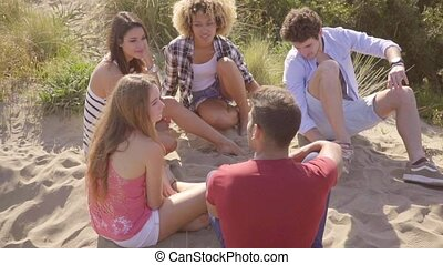 Five friends sitting on beach dune and chat - Five young...