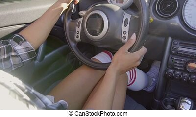 Close up on woman knees while driving a car - Close up on...