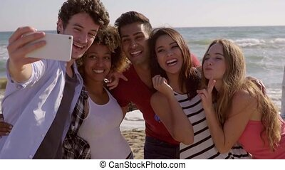Friends making selfie pictures at the seaside - Group of...