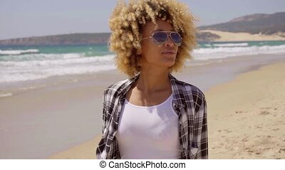 Attractive young woman in trendy sunglasses with a curly...
