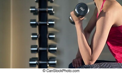 Woman doing exercise with barbell in the gym. - Sportive...