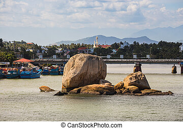 Boats and rocks near fishing village on the river Kai in Nha...