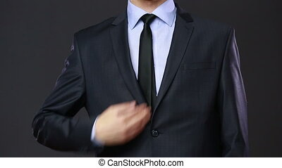Firearms and security topic: a man in a black suit holding a gun