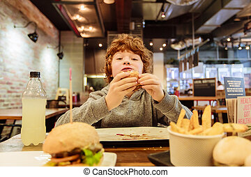 Hungry boy eats burger in restaurant - Hungry caucasian...