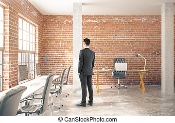 Man in red brick office - Thoughtful businessman in...