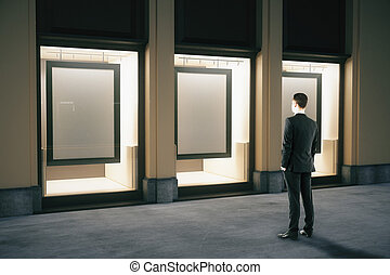 Showcase with frames and businessman - Side view of shop...