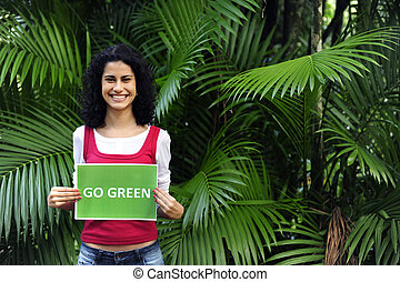 environment conservation: woman in the forest holding a go green sign