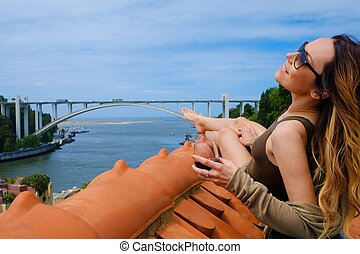 Woman enjoying sunbath with glass of port wine on the...