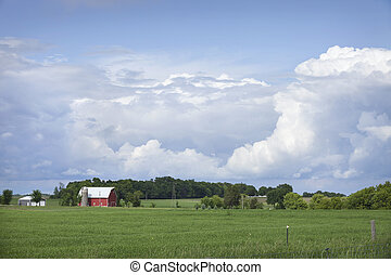 Red barn and field below dramatic cloudscape - A red barn...