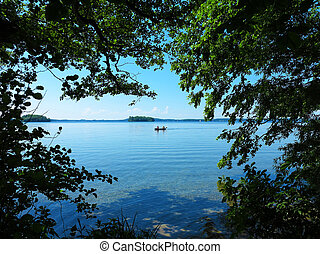 lonsome lake with islets and boat - idyllic lake view with...