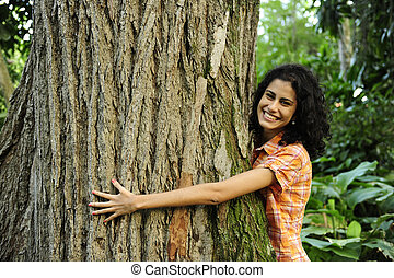 In love with nature: woman hugging a tree in the forest - In...