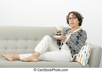 mature woman drinking tea on the sofa - mature woman with...