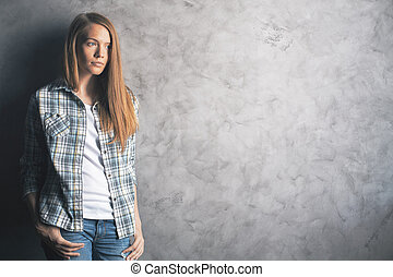 Thinking woman against concrete wall - Casually dressed,...