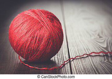 red ball of threads on wooden table
