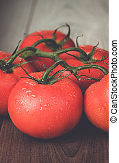 fresh tomatoes on the brown wooden table - fresh red...