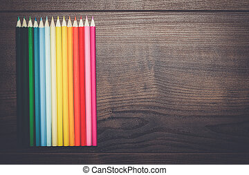 colorful pencils over brown wooden table background -...