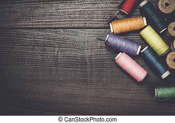 threads on brown wooden table background - threads on the...