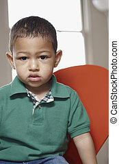 Sullen little boy - Mixed race toddler sitting and looking...