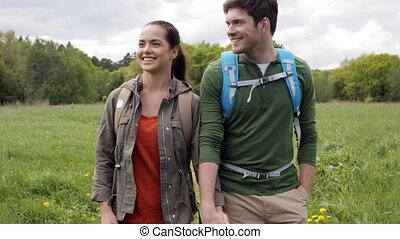 happy couple with backpacks hiking outdoors - travel,...