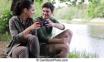 happy couple with cups drinking in nature 7 - travel,...