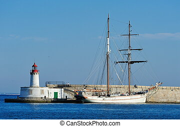Sailboat in the harbor of Ibiza - Lighthouse and sailboat in...