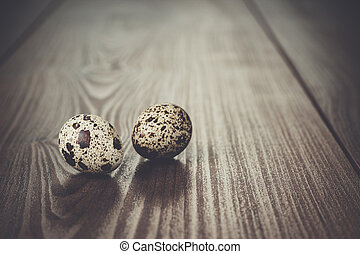 quail eggs on the brown wooden table - two quail eggs on the...