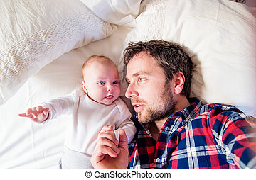 Baby boy lying on bed, next to his father - Cute newborn...
