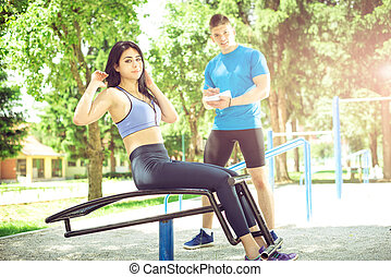 Woman doing sit ups outdoor with her trainer - Young adult...