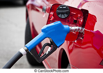 Blue Gas Nozzle Fueling Red Car - Horizontal shot of a blue...