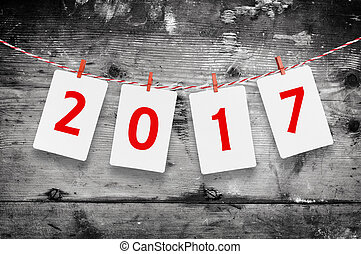 Paper or photo frames with 2017 figures hanging on the red striped rope . New Year design. Wooden background.