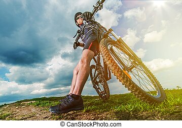 Extreme Mountain Biker Resting on His Bike During Trail...
