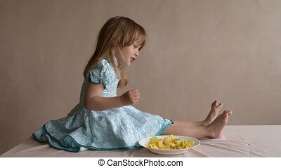 Girl with potato crisps stirring her toes - Little girl with...