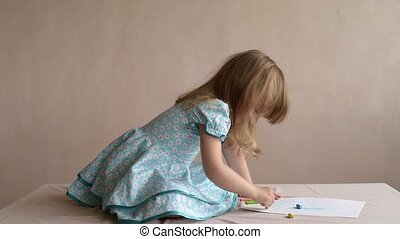 Little girl drawing on a table.