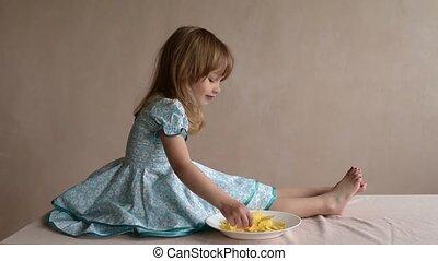 Little girl eating crisps on a table