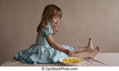 Girl eating crisps and jerking her leg