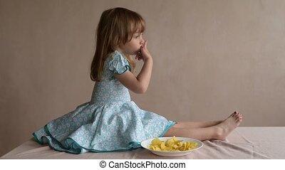 Little girl licking her fingers - Little girl sitting on a...