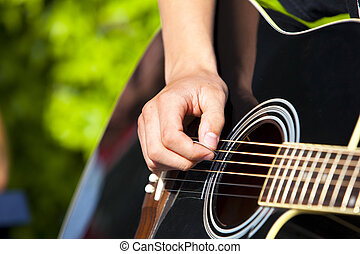 playing a black accoustic guitar
