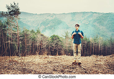 Hiker man standing in the forest - Hiker young man with...