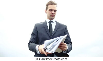 businessman standing with a stack of paper in the wind...